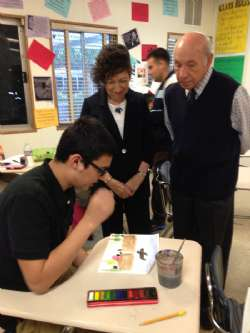 A student explains to Holocaust Survivors Gabriella Karin and David Lenga the theory behind his artwork.